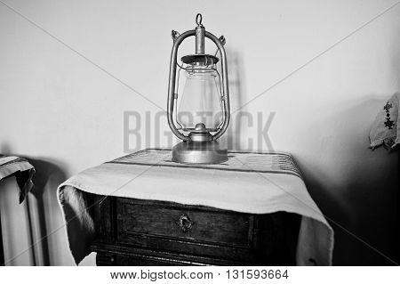 Old Kerosene Lamp On The Table. Black And White Photo