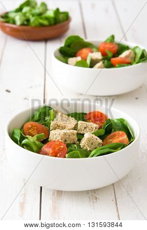 Vegan tofu salad with tomatoes and lamb's lettuce on white wood background