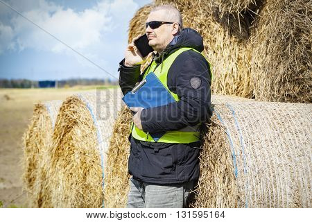 Farmer talking on smartphone at the hay bales