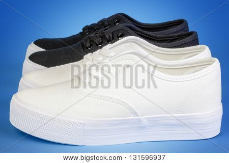Two pairs Flatform Plimsolls in white and black on blue