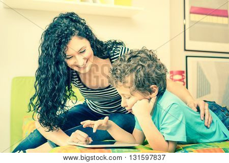 Young mother having fun with son using tablet on bed - Learning computer tech with sister in children room - Teacher showing boy how to interact on modern device - Vintage filter and focus on kid face