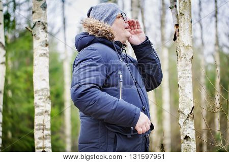 Man yelling in woods in autumn day
