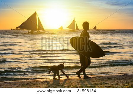 Modified silhouette of unrecognizable surfer with kid in Boracay during sunset - Father and son walking at the beach - Exclusive travel fun destination in Philippines - Warm enhanced filtered look