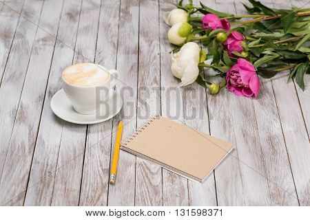 Notebook with a pencil next to coffee and peonies flowers on the wooden background.
