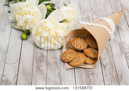 Cookies and pionies flowers on the white wooden background. Place for text.
