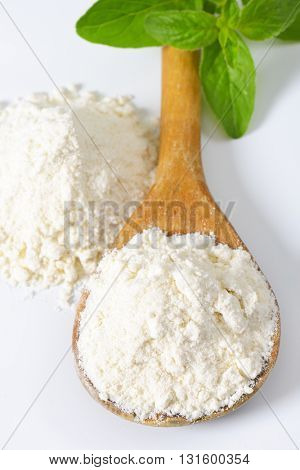 wooden spoon of wheat flour on white background - close up