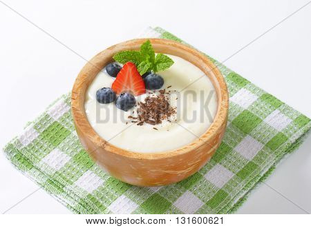 bowl of semolina pudding with fruit and grated chocolate on checkered dishtowel