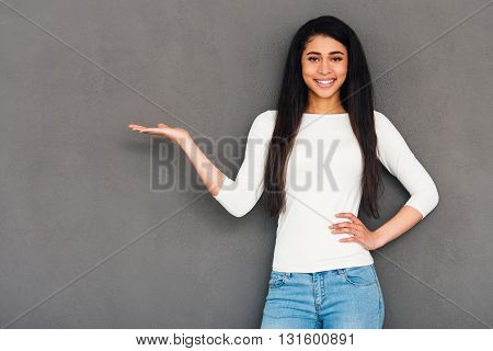 Copy space in her hand. Attractive young African woman holding copy space and looking at camera with smile while standing against grey background