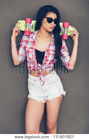 Enjoying her carefree style. Beautiful young mixed race woman carrying skateboard on shoulders and looking away while standing against grey background