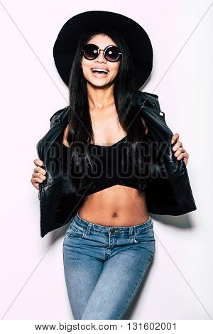 Enjoying her style. Beautiful young mixed race woman in leather jacket and hat posing against white background and expressing positivity