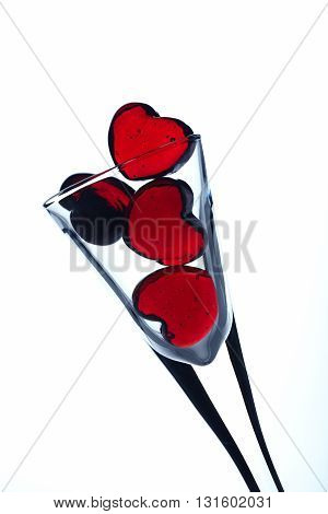 Red glass hearts in glass on white background