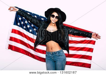Young and carefree. Beautiful young mixed race woman carrying American flag and smiling while standing against white background