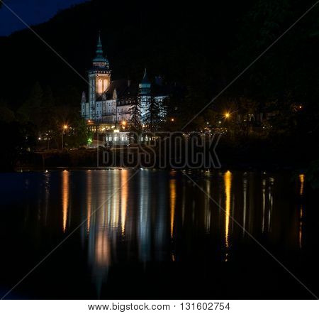 Lillafured palace at night time. Illuminated building reflects in lake.
