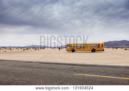 29 Palms, California/USA-03/21/2016: School Bus in the desert, 29 palms,  Boy is walking towards the horizon.