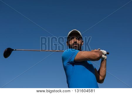 golf player hitting shot with club on course at beautiful morning with sun flare in background
