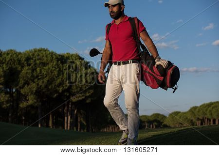 handsome middle eastern golfer  carrying  golf bag  and walking at course to next hole
