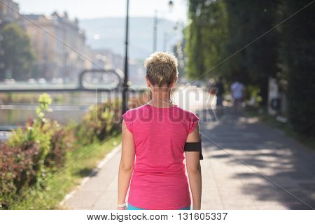 jogging woman setting music and running route on  smart phone putting  earphones before morning run