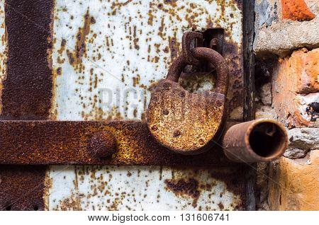 Iron Old Rusty Lock Hanging On The Iron Door.