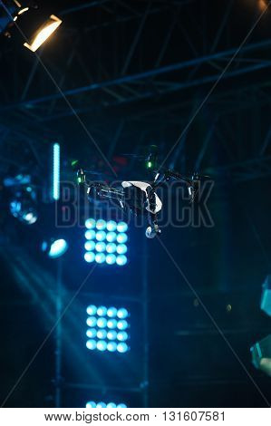 White drone with four propellers and professional camcorder flies over the stage