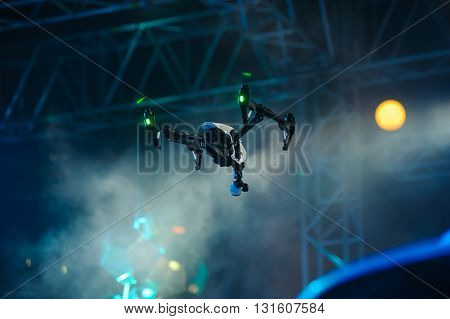 Professional drone with video camera hanging in the air during show