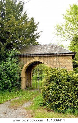 Stone portico of size with an arch and an iron railing to forge.