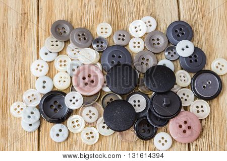 Various sewing buttons on a wooden table