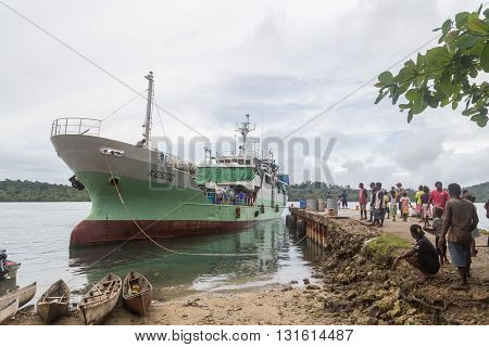 Seghe, Solomon Islands - June 16, 2015: Ship anchored at Seghe harbor and local people waiting.