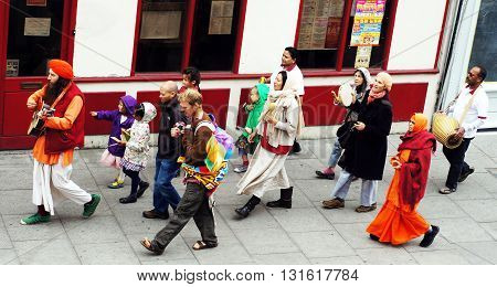 LONDON, UK - MAY 21, 2016: Hare Krishna followers walk and sing in a street in London.