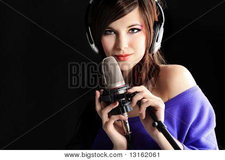 Toma de una mujer bastante joven en auriculares cantando una canción con un micrófono. Rodada en un estudio.
