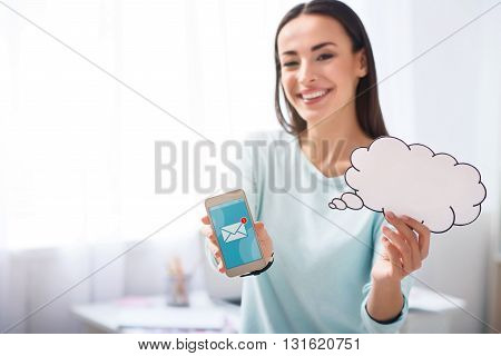 Modern communication. Selective focus of smart phone in hands of pleasant delighted woman holding it and smiling while expressing gladness
