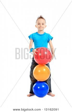 Portrait of a cute sporty boy standing with balls. Isolated over white background.