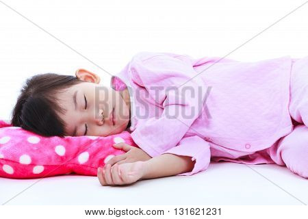 Healthy children concept. Little asian child sleeping peacefully. Adorable girl in pink pajamas taking a nap on white background.