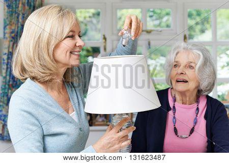 Female Neighbor Helping Senior Woman Change Lightbulb In Lamp