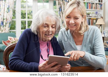 Female Neighbor Showing Senior Woman How To Use Digital Tablet