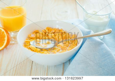 boul with corn flakes and spoon in it and blue napking on a table