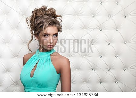 Studio portrait of a sexy blond in blue dress, over leather upholstery background. Elegant luxury woman with a seductive neckline and bare shoulders looks into the camera.