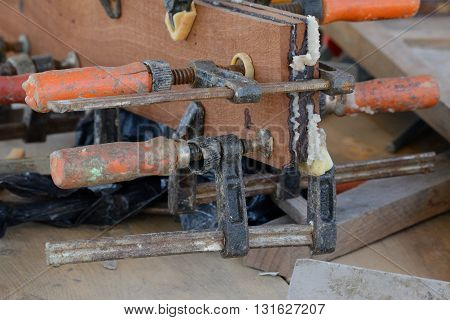 Clamps holding together wood on a workbench at a boatyard