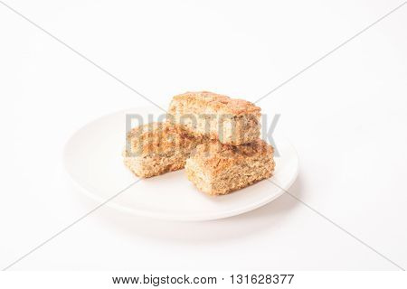 Three pieces of rusks in a stack on a white plate all on an isolated white background.