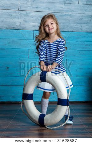 litl girl holding a life preserver looking at camera