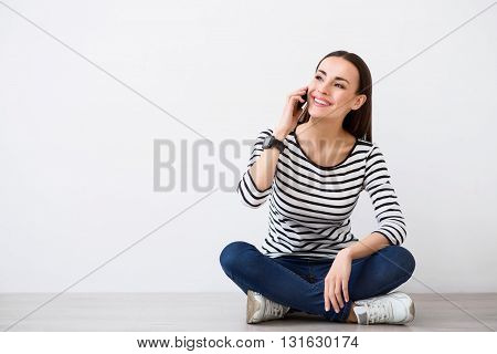 Be part of the world. Pleasant cheerful charming woman talking on cell phone and expressing positivity while sitting on the floor