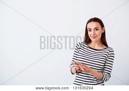 Positive glance.  Pleasant delighted charming woman holding cell phone and looking at you while standing isolated on white background