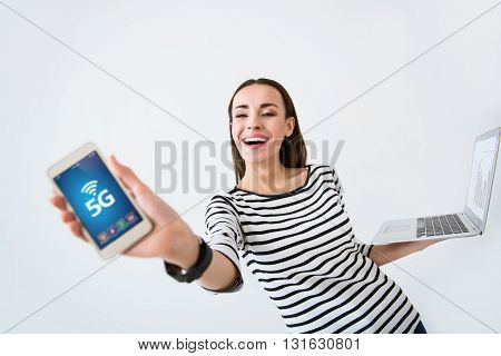Express yourself. Overjoyed beautiful smiling woman holding laptop and cell phone while expressing gladness on white background