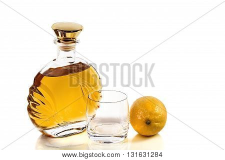 Bottle of whiskey and an empty tumbler with lemon on a white background