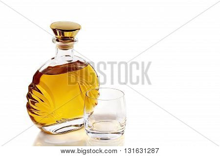 Bottle of whiskey and a tumbler on a white background