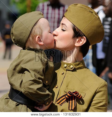 Orel Russia - May 9 2016: Celebration of 71th anniversary of the Victory Day (WWII). Mama kissing her baby in military uniform closeup