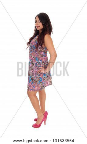 A beautiful young East Indian woman standing full length in a colorful summer dress isolated for white background.