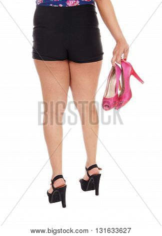 A closeup image of the legs and butt of a young woman holding her high heels isolated for white background.