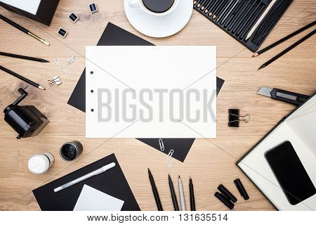 Top view of blank white paper sheet black stationery items several drawing tools coffee cup and smart phone on wooden desktop. Mock up