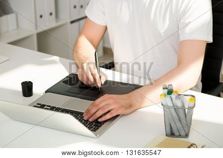 Man using laptop and graphic tablet on white office desktop with several items