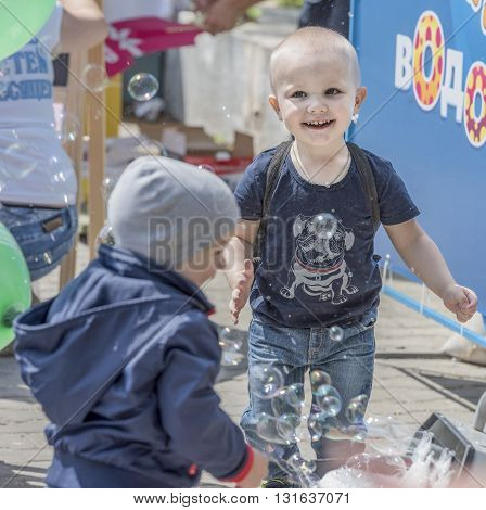 Rostov-on-Don Russia- May 22, 2016: Boy catches soap bubbles on holiday